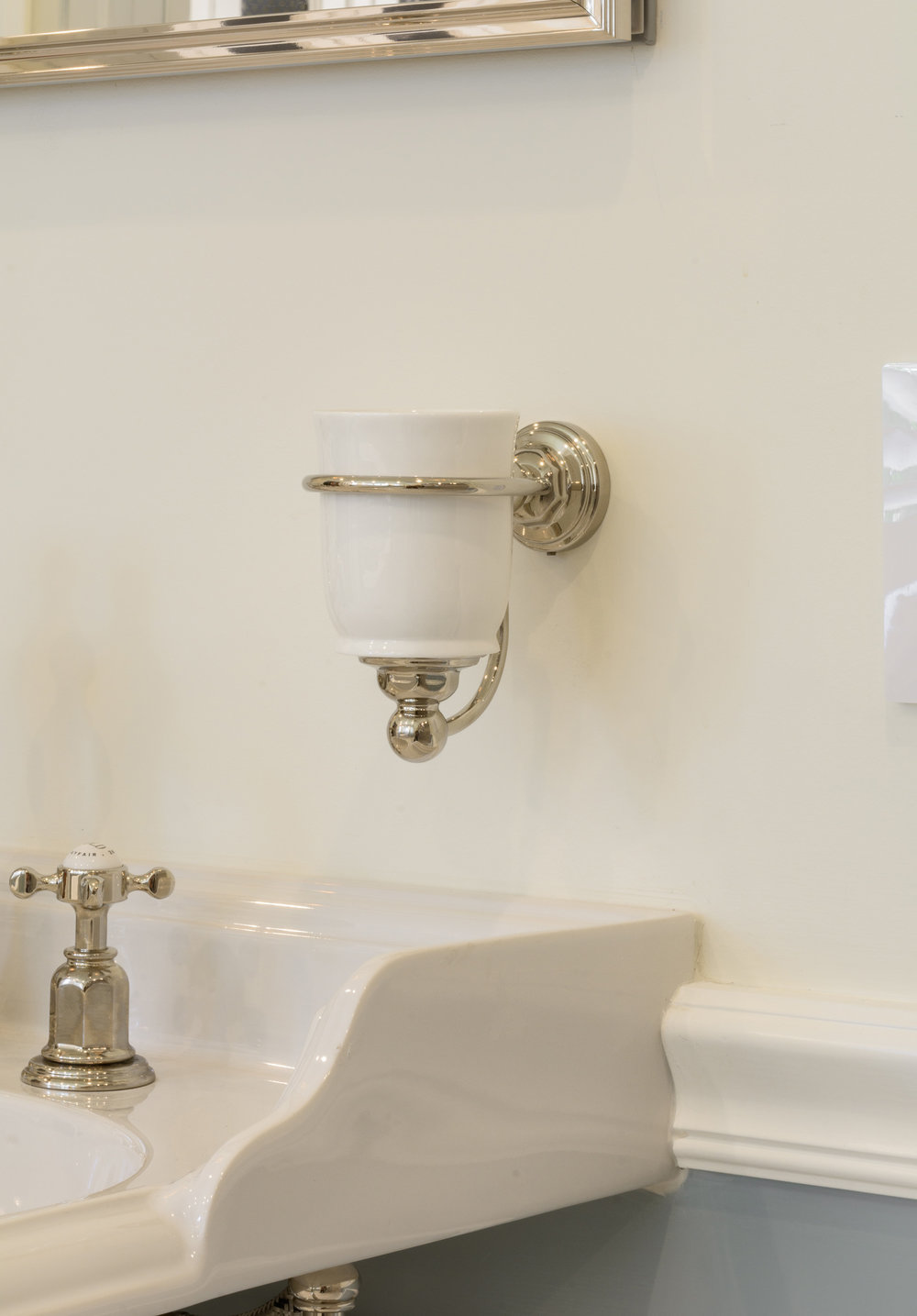 Polished nickel and white ceramic wall-mounted toothbrush holder over console sink