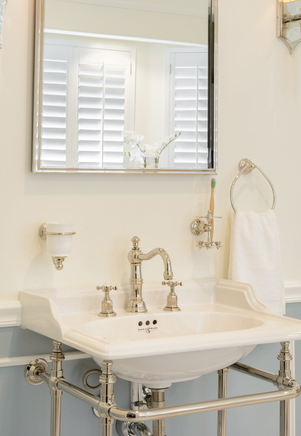 Victorian sophistication: white console sink, traditional widespread faucet, framed mirror, white wall with soft grey wainscot