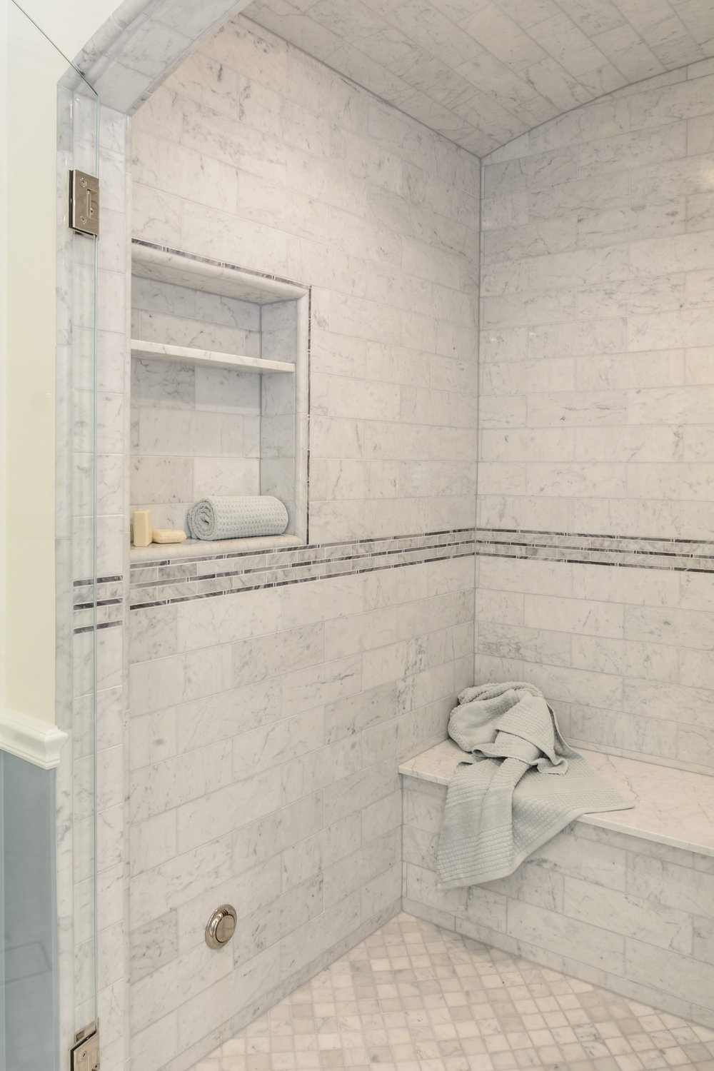 Calm retreat: soft grey carrera marble arched shower with bench and niche