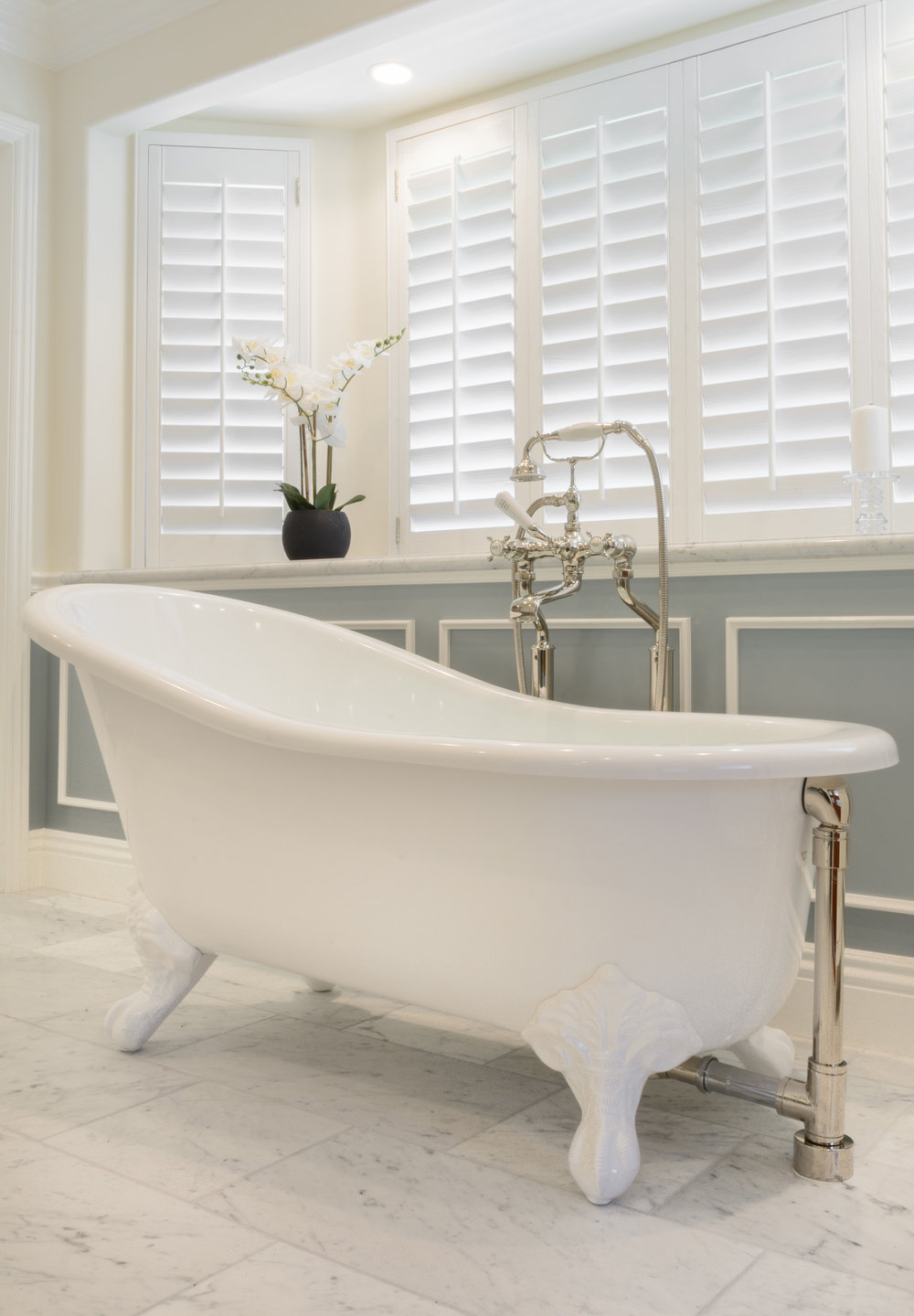 Crisp white clawfoot bathtub, soft grey carrera marble floor, large bay window with white interior shutters, overhead lighting and overall soft neutral colors provide for a relaxing experience