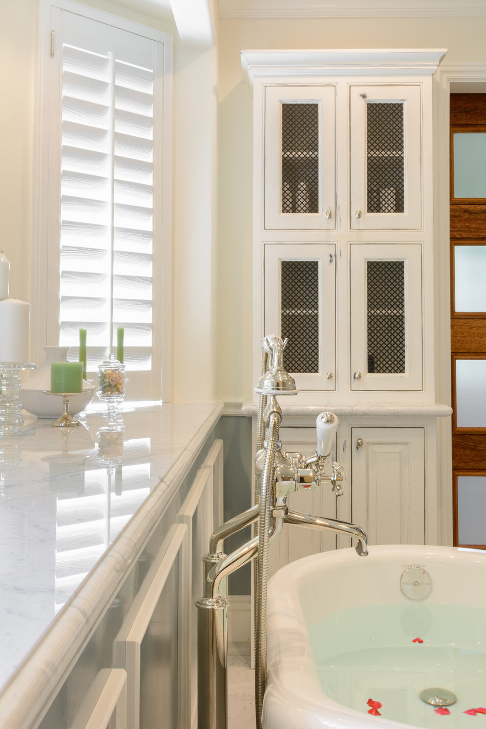 Marble slab bay window counter, traditional polished nickel tub filler and distressed white bathroom cabinets