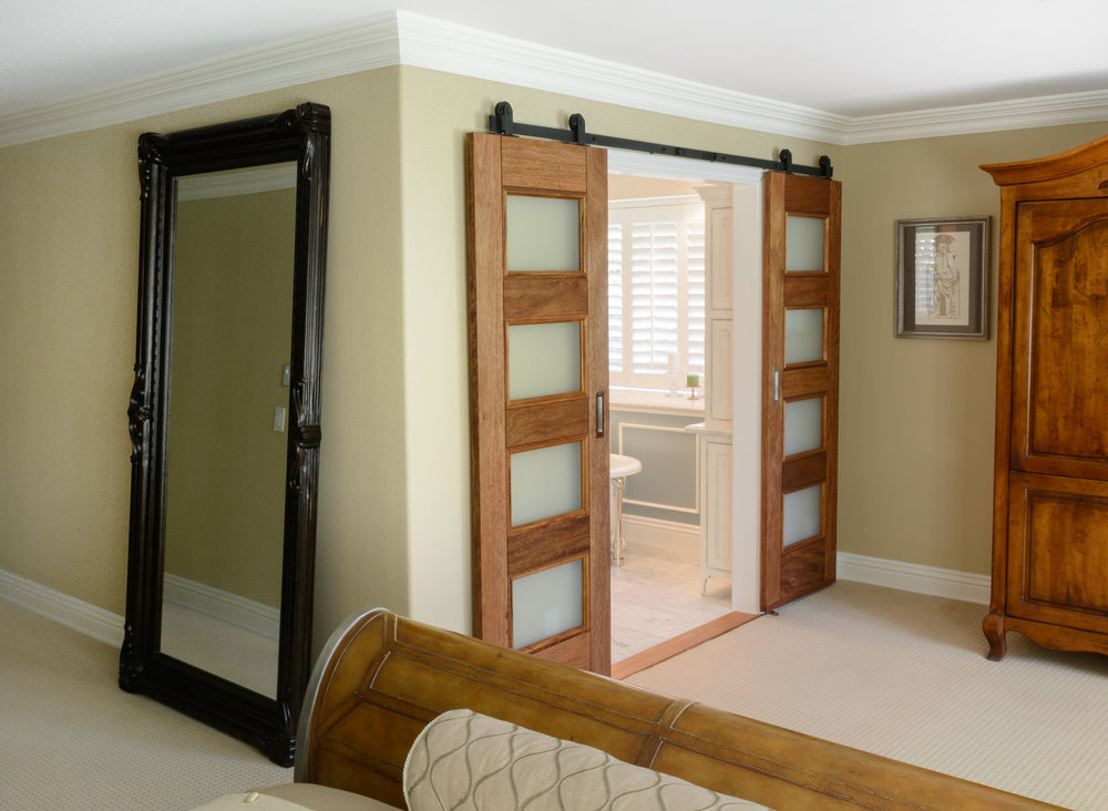 Mahogany barn doors with frosted glass open the master suite onto the Victorian style master bathroom