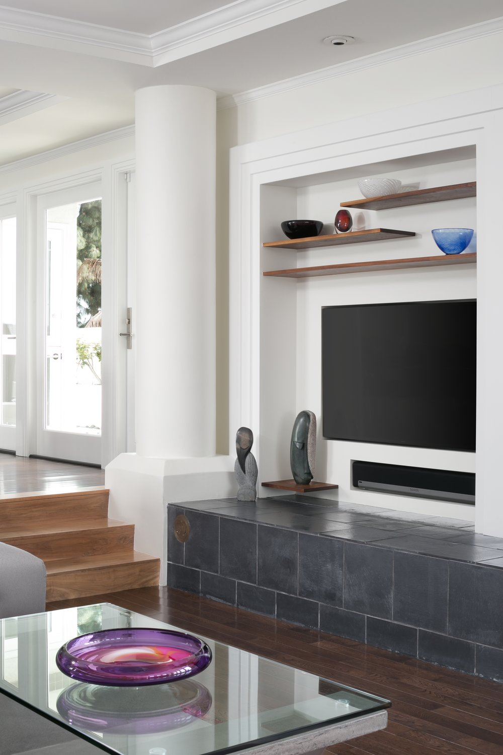 This post-modern living room features a built-in entertainment center with floating walnut shelves and a matte tile bench