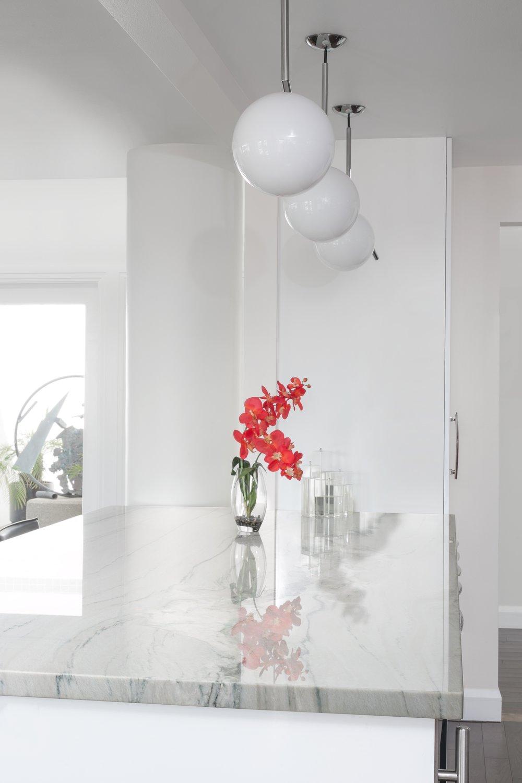 Post-Modern-Update-Peninsula-Pendant-Lights-White-Cabinets-Stone-Counter-Top.jpg