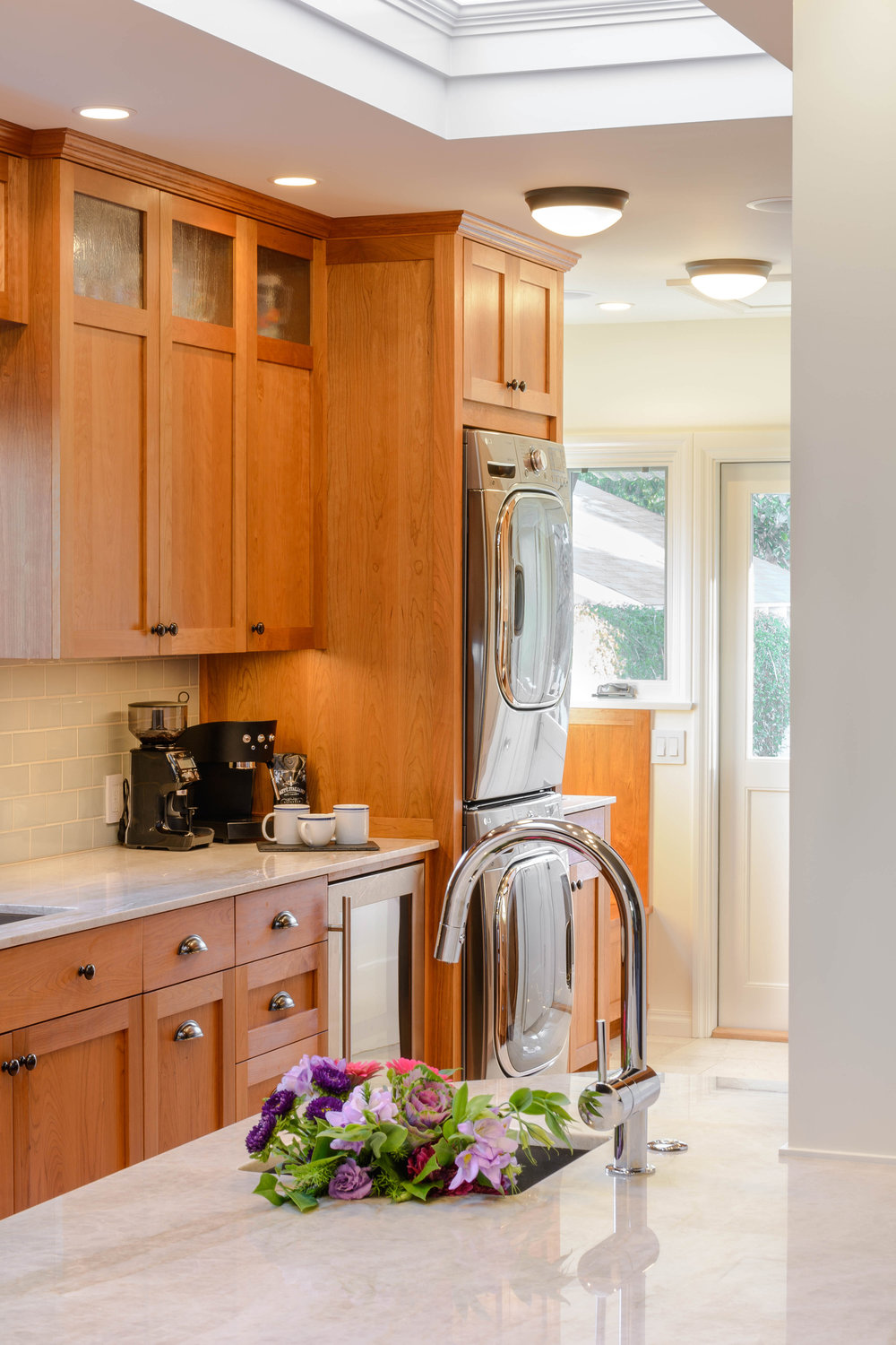 Bright Tudor style kitchen with a mudroom, a built-in washer and dryer, and a peninsula with a prep sink