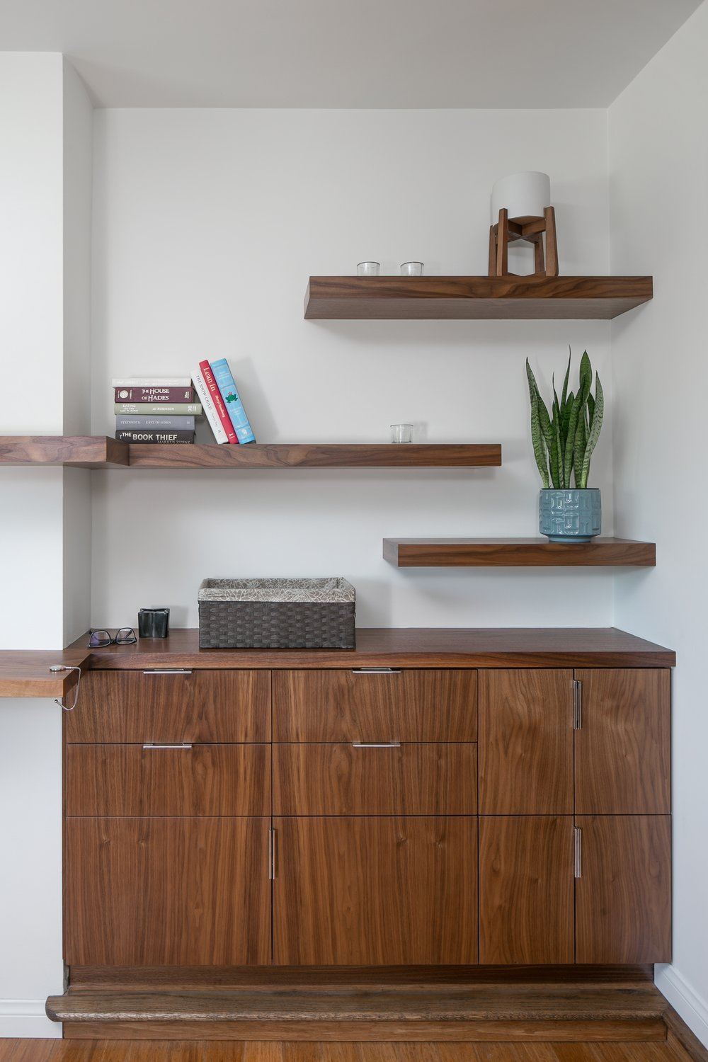Built-in walnut cabinet and floating shelves