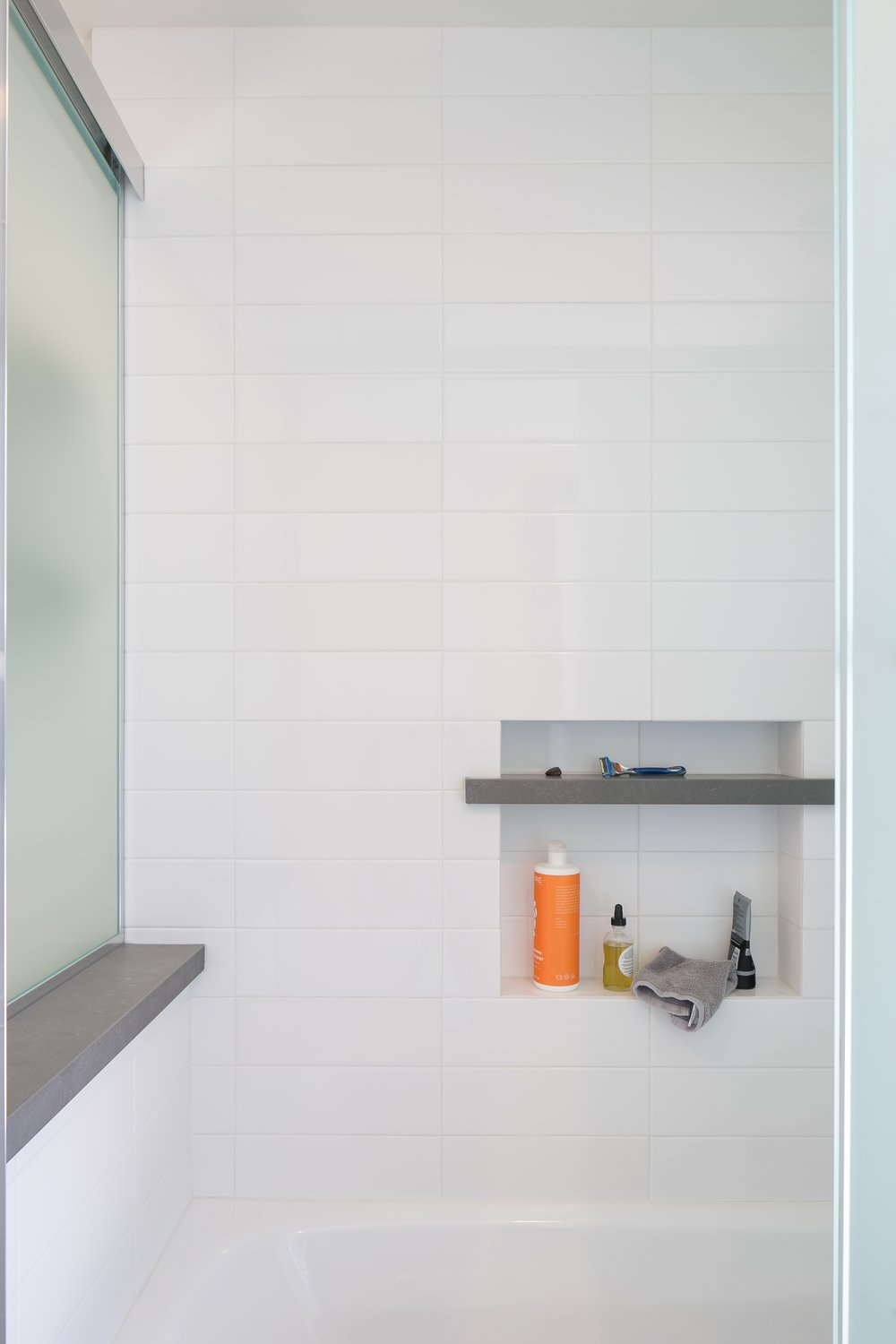 Bathtub niche: white gloss tiles and a grey matte contrasting stone