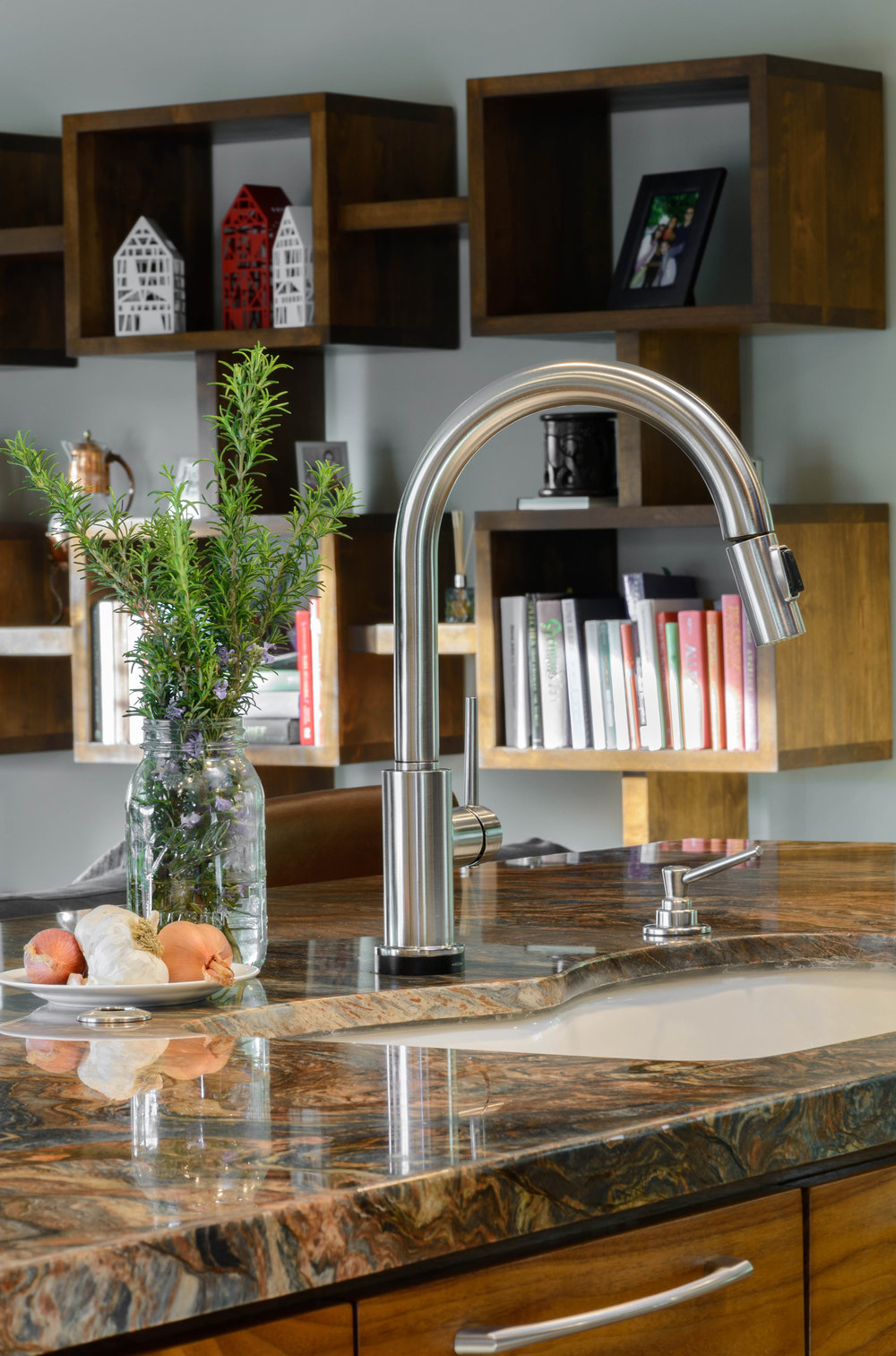 Island sink combined with a contemporary single-hole deck-mounted gooseneck faucet and a built-in soap dispenser