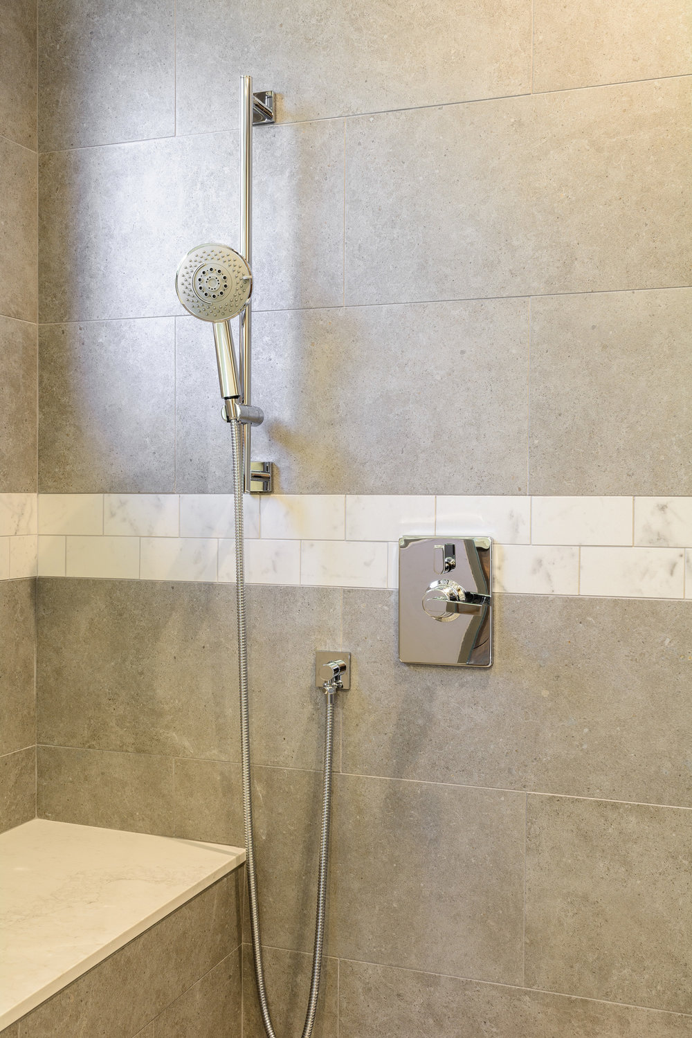 Grey shower wall with chrome shower valve and hand held fixture