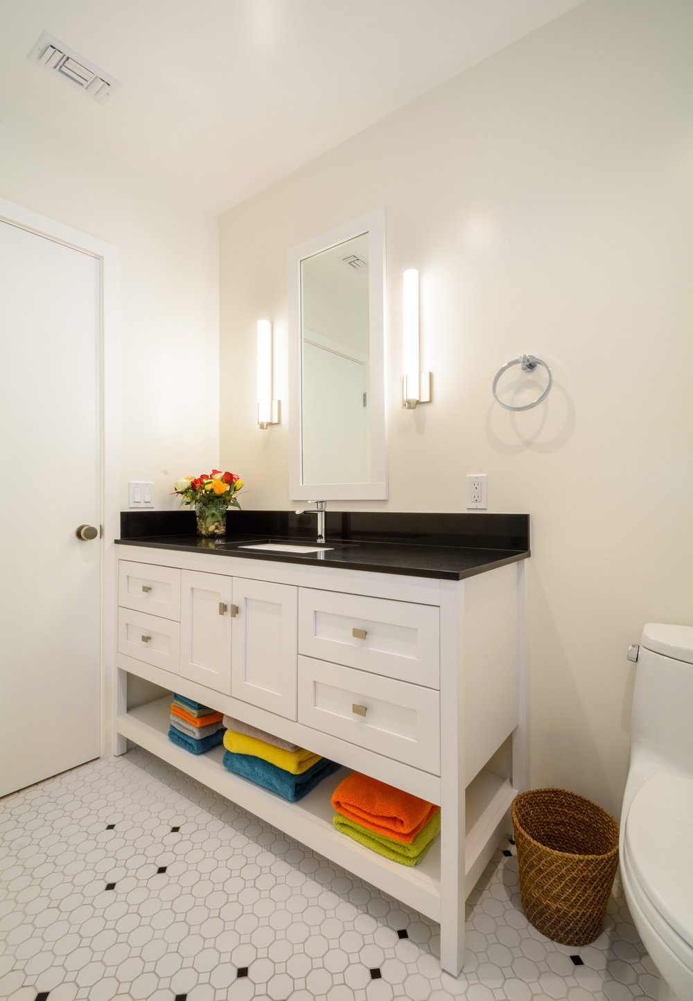 White, black and a touch of color: this guest bath features a white vanity with an absolute black granite top and a floor of white octagon tiles and black dot accent tiles set in a unique pattern