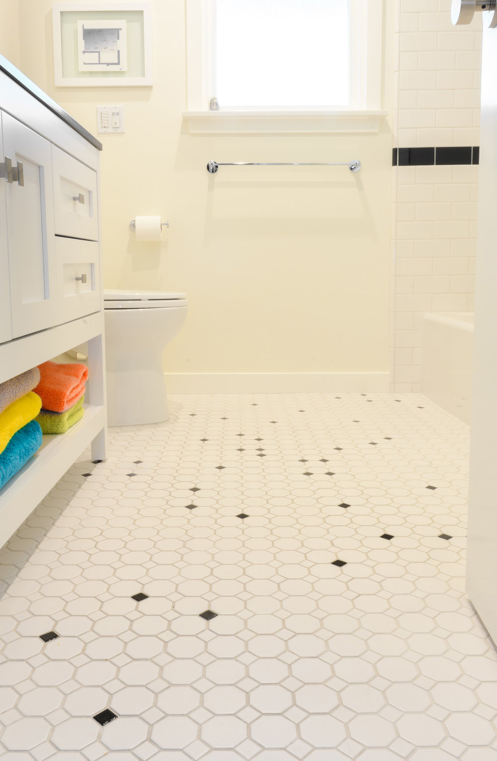 All white bathroom remodel using black accent border and black octagon dots on floor to mimic the constellations in the Northern sky