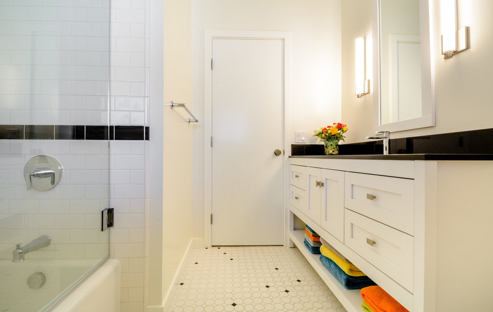 White subway tile tub surround with black border and custom shaker style vanity with black top