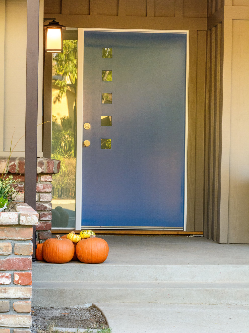 Modern blue front door with square lites for this mid-century ranch remodel