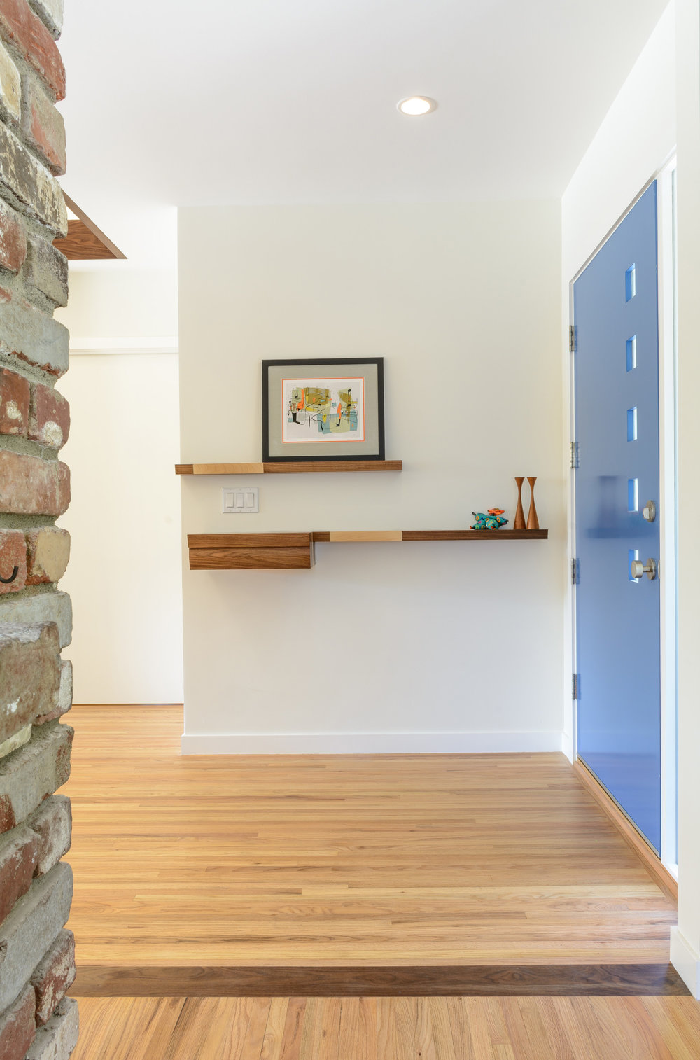 A continued welcome: bright open foyer with white walls, recessed lighting, the blue modern front door with square lites, walnut and maple floating shelves and accent floor pieces