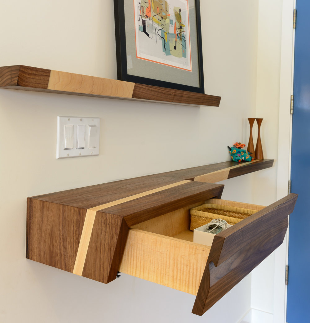 Discreet entryway storage offered by custom-built walnut and maple floating shelves