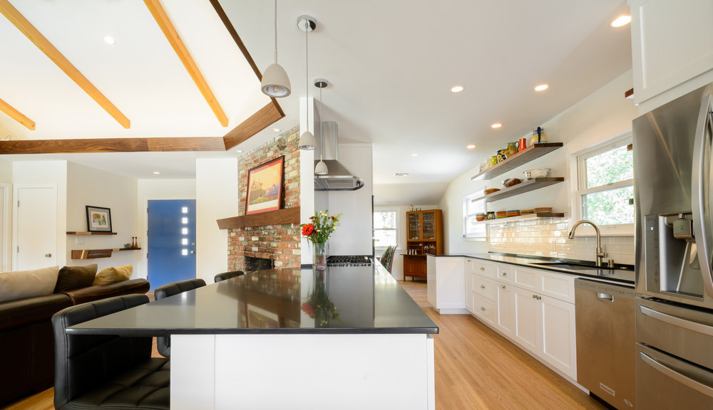Mid-century ranch kitchen remodel with a black quartz countertop allowing for bar seating at the peninsula
