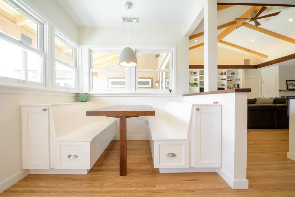 The perfect breakfast nook with white shaker cabinets and a walnut table surrounded by double hung windows: bright, warm, inviting, and a subtle way to maximize storage space