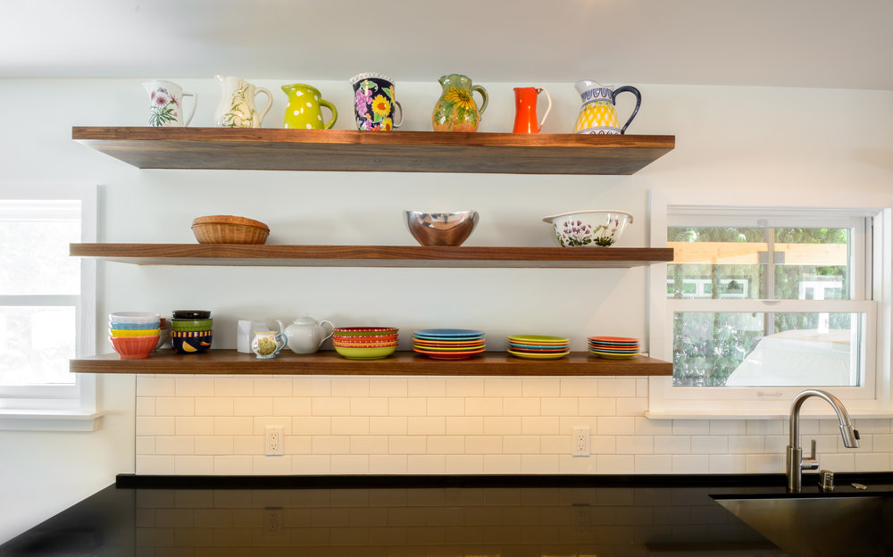 Open kitchen shelving: walnut floating shelves over black quartz countertop and white subway tile
