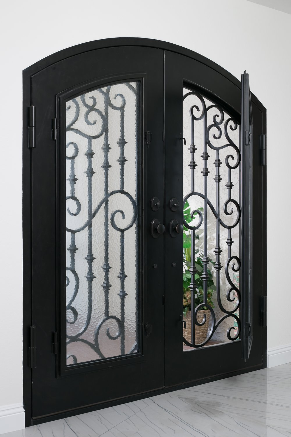 The double steel front door with wrought iron ornamental detail and interior glass doors combined with the slab entry floor provide for a magnificent foyer