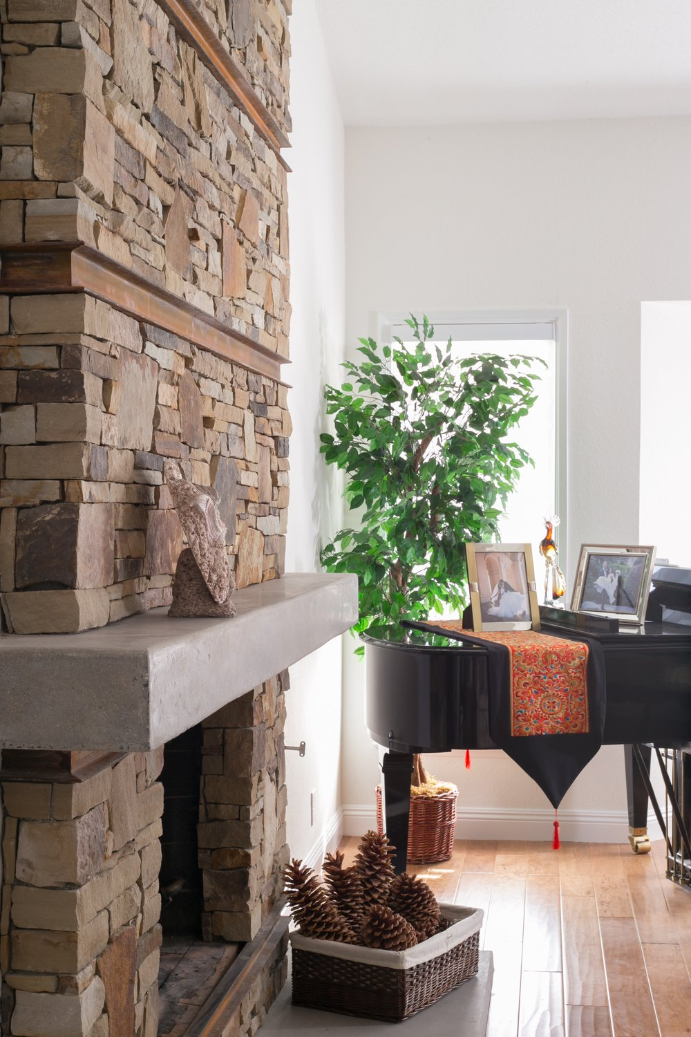 Extra warmth: stacked stone fireplace surround with rusted channels and a polished concrete mantel and hearth