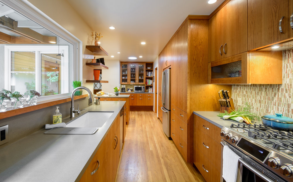 Bright contemporary kitchen with sleek lines, cherry cabinets, grey quartz countertops, stainless steel appliances, under the cabinet lighting, LED recessed lighting and a picture window