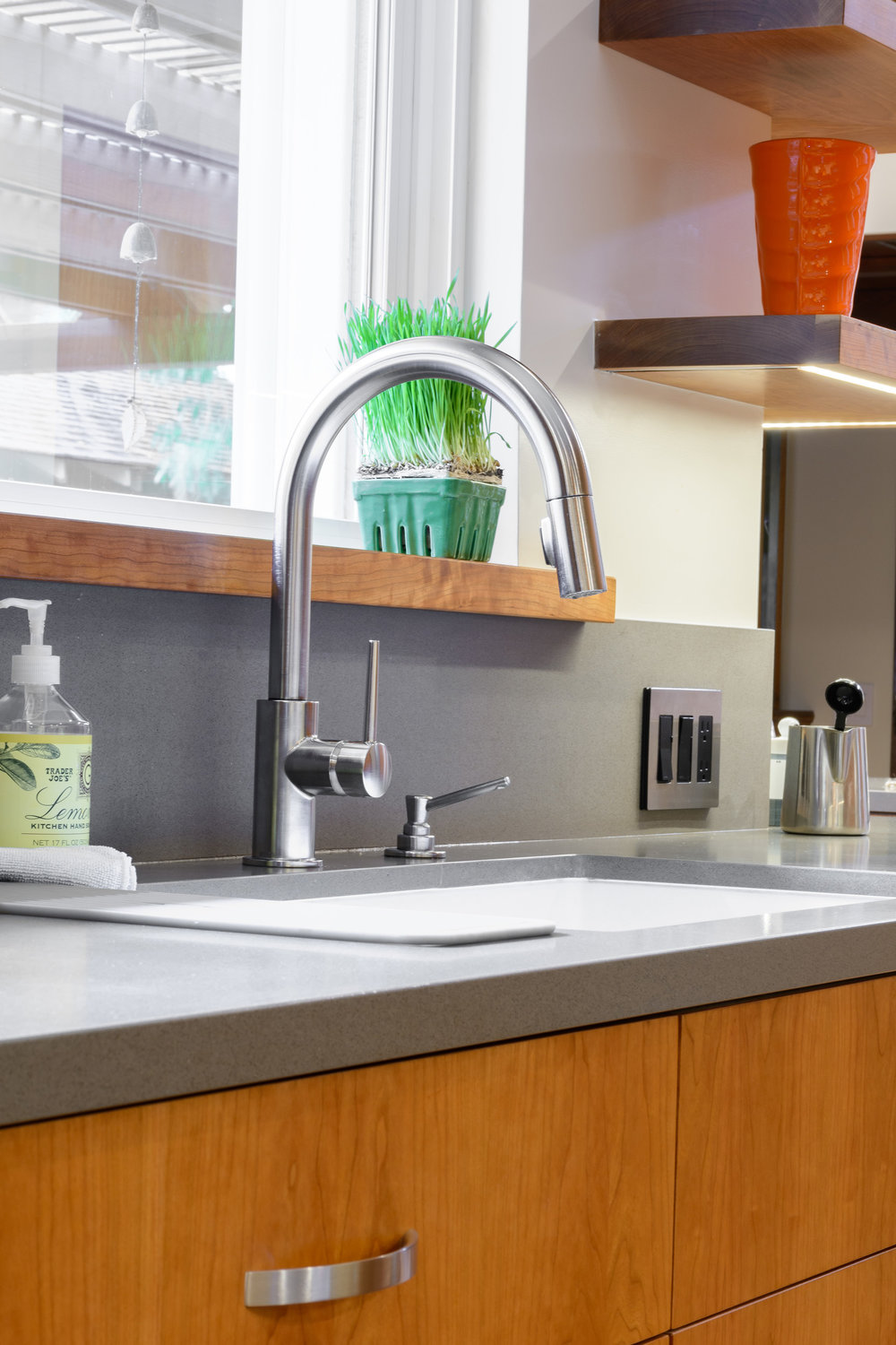 Contemporary kitchen gooseneck faucet deck-mounted on a grey quartz countertop and assorted with a built-in soap dispenser in front of a picture window
