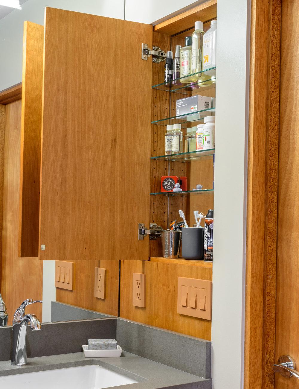 Custom cherry medicine cabinet built into wood wall