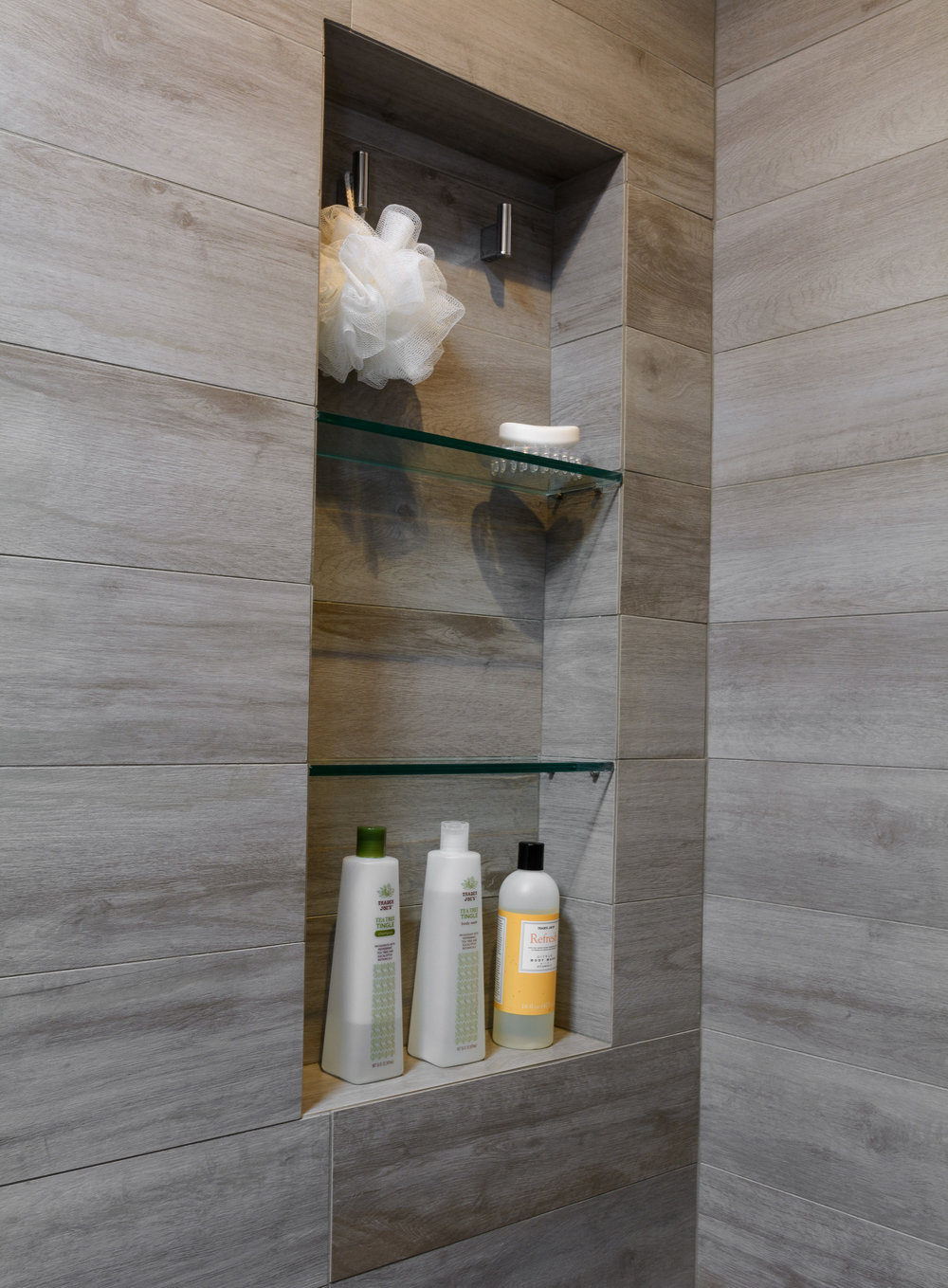 Tile niche in shower with glass shelves featuring weathered wood tile