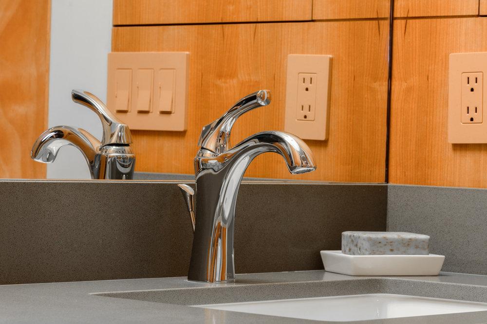 Sleek single hole bathroom sink faucet deck mounted on a grey vanity top