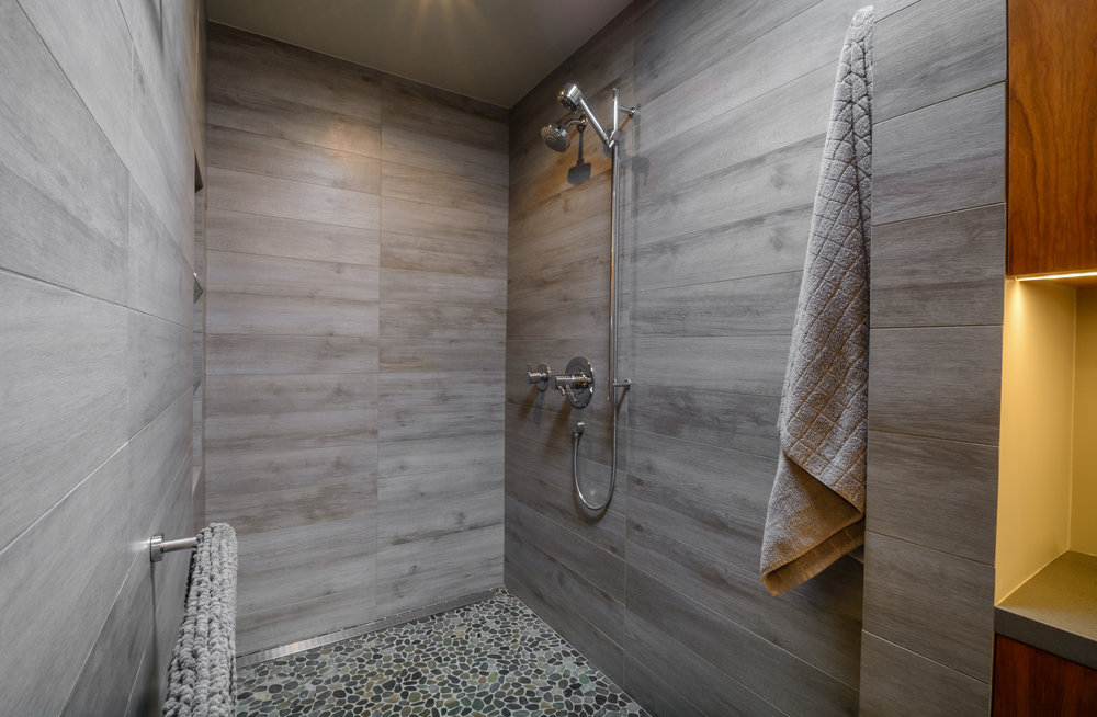 Open walk in shower with pebble tile floor and weathered wood looking tile