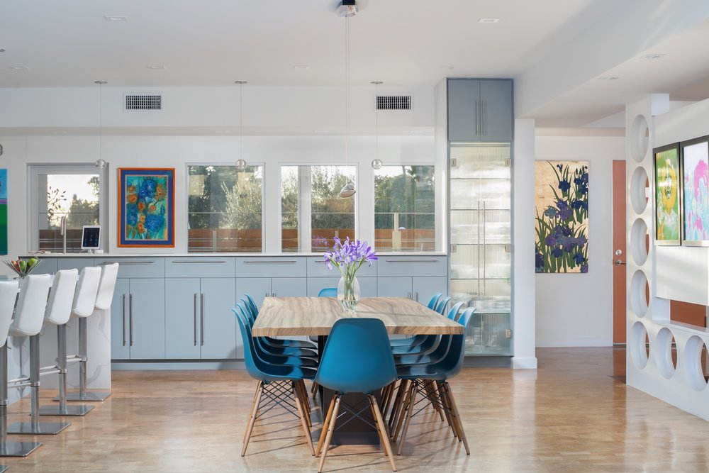 Bright mid-century dining room with an open floor plan, large picture windows, grey cabinets, quartz countertops and the perfect colorful art touch