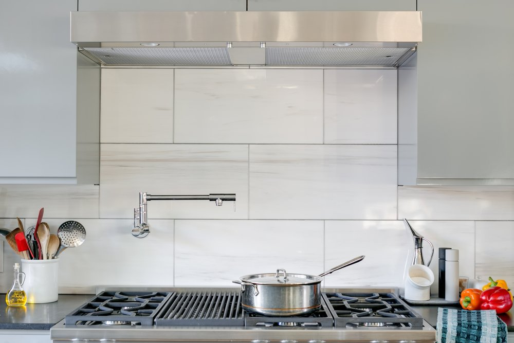 Range top and under cabinet hood with a marble backsplash