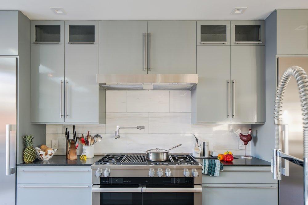 Mid-century modern kitchen luxury: grey cabinets, marble backsplash and stainless steel appliances