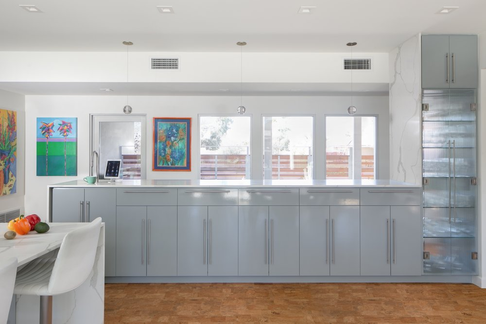 This sidebar cabinet with a quartz waterfall countertop and a reeded glass stemware cabinet has the perfect lines to complement the rest of this modern mid-century kitchen and dining room