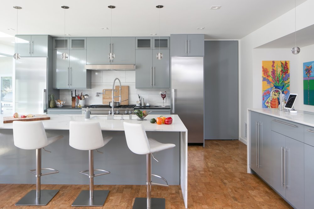 The sleek soft grey kitchen cabinets and island design with white engineered stone waterfall countertops combined with the stainless steel appliances create a seamless flow