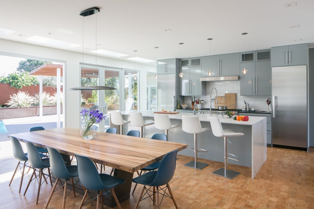 Beautiful and bright mid-century modern kitchen and dining room opening onto outside patio