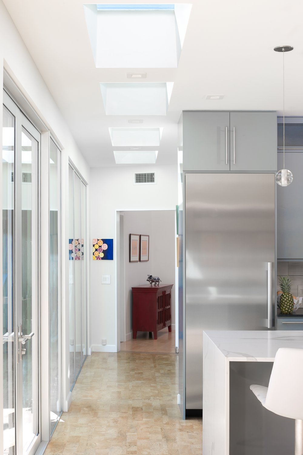 The hallway design with skylights, picture windows, patio doors and cork flooring creates an open and inviting space