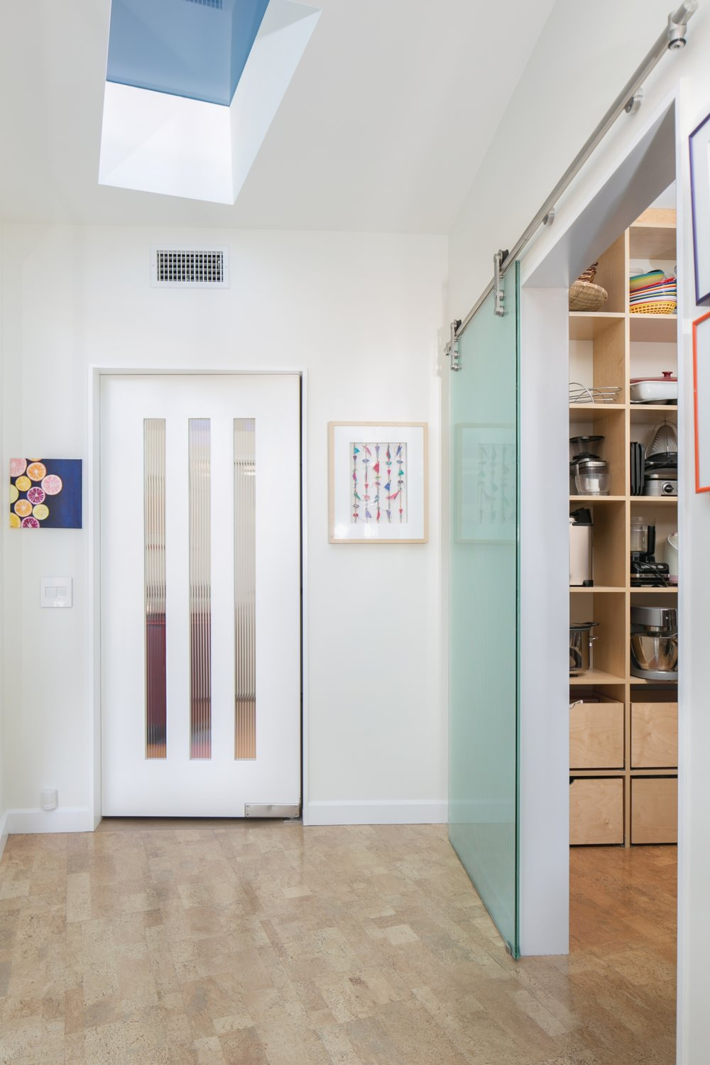 Mid-century modern kitchen remodel with a reeded glass barn door leading to the pantry