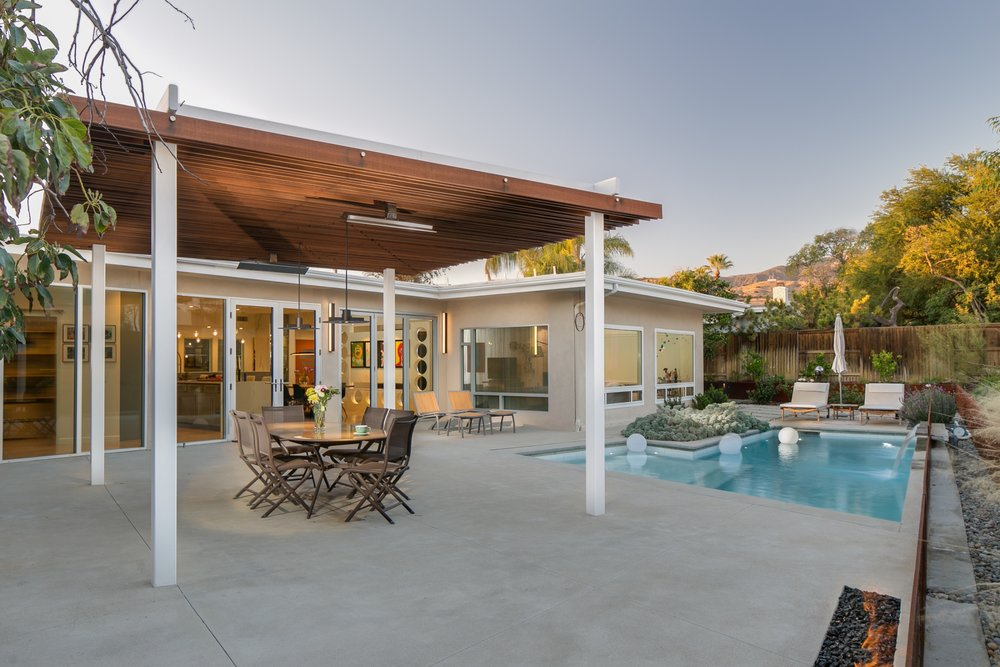 Mid-century modern outdoor living: dining under the pergola, next to the pool, while enjoying the view and the warmth of the fire pit