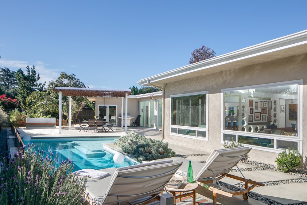 Mid-century modern outdoor living: lounging next to the pool while enjoying the view and the aromas