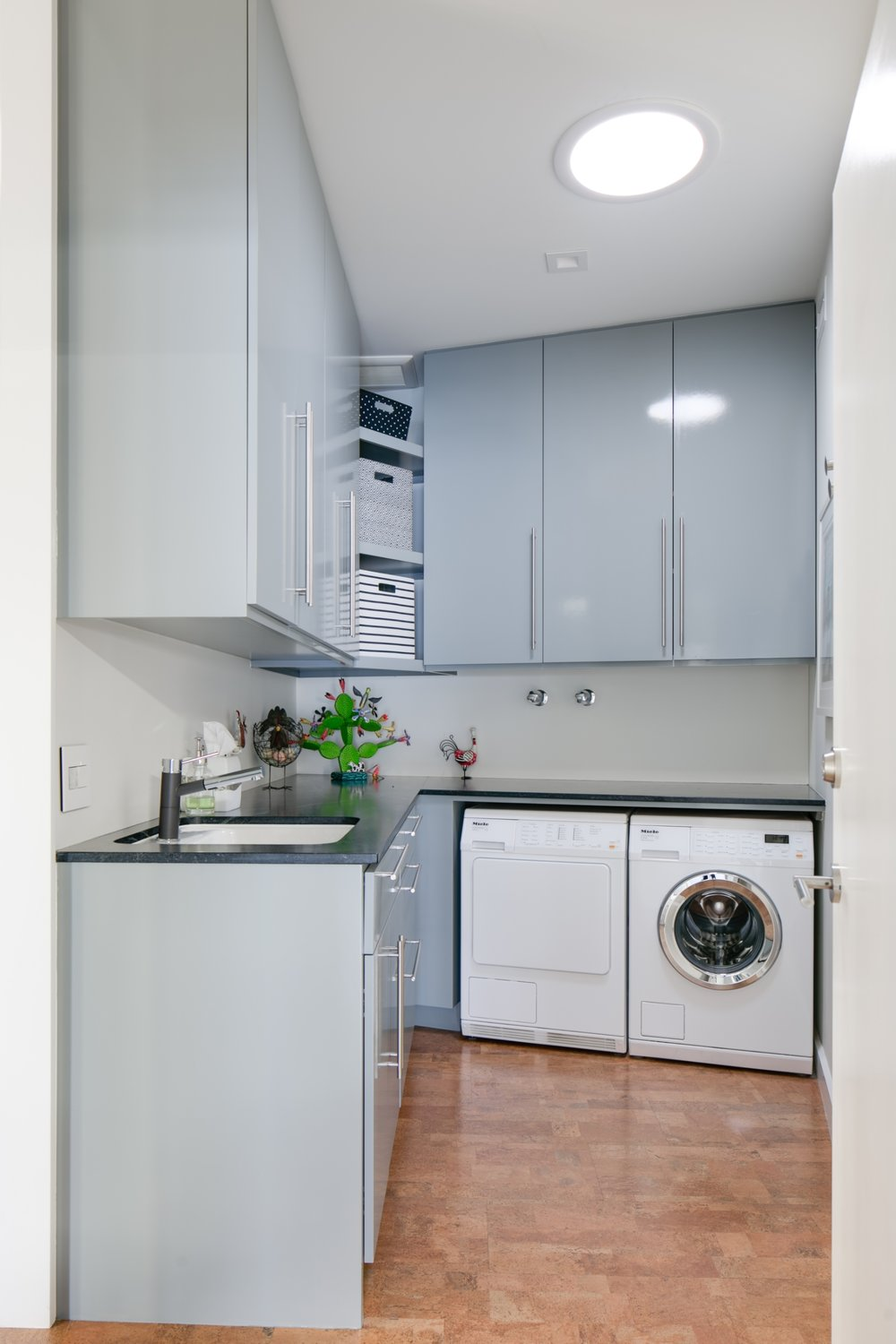 Mid-century modern laundry room with sleek gray cabinets, black quartz countertops and cork floor