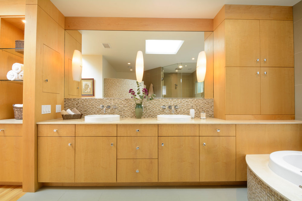 The spacious maple cabinetry of this master bathroom offers a luxurious feel and ample storage space