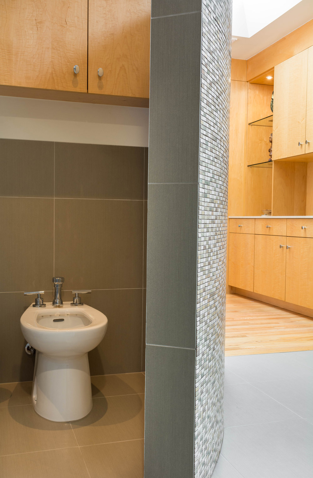 White bidet next to curved mosaic tile privacy wall and modern large-format tile wainscot