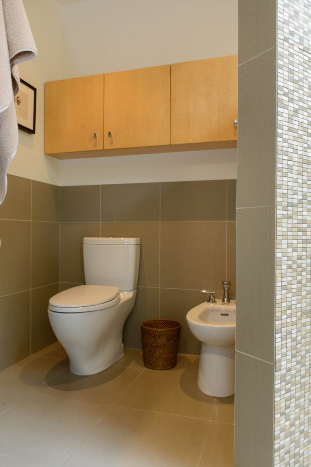 Toilet and bidet hidden by curved mosaic tile privacy wall