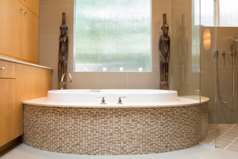 This spa-like white tub set in a curved mosaic tile base with a rain glass window wrapped in tile behind it is the focal point of the master bathroom
