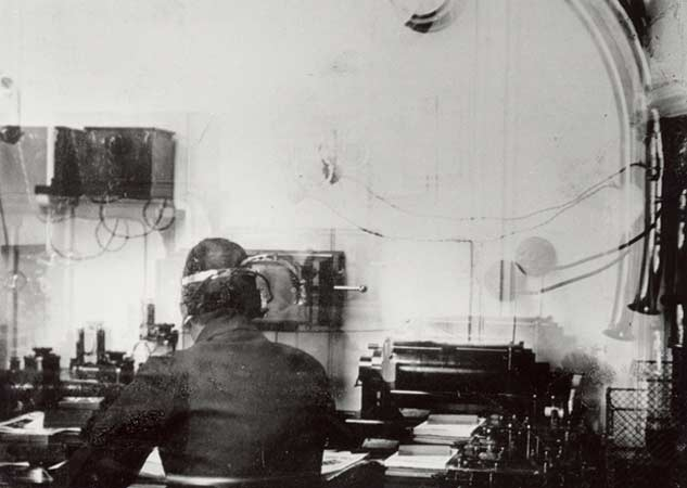 The only known photograph of Titanic's wireless room. The operator is most likely Harold Bride aged 21.