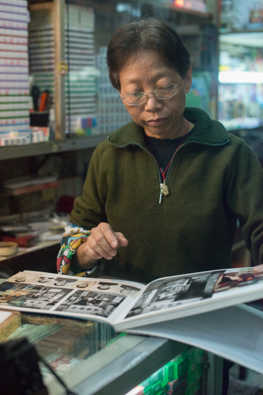Mrs. Ho Sau Mei looking at some old images of her craft