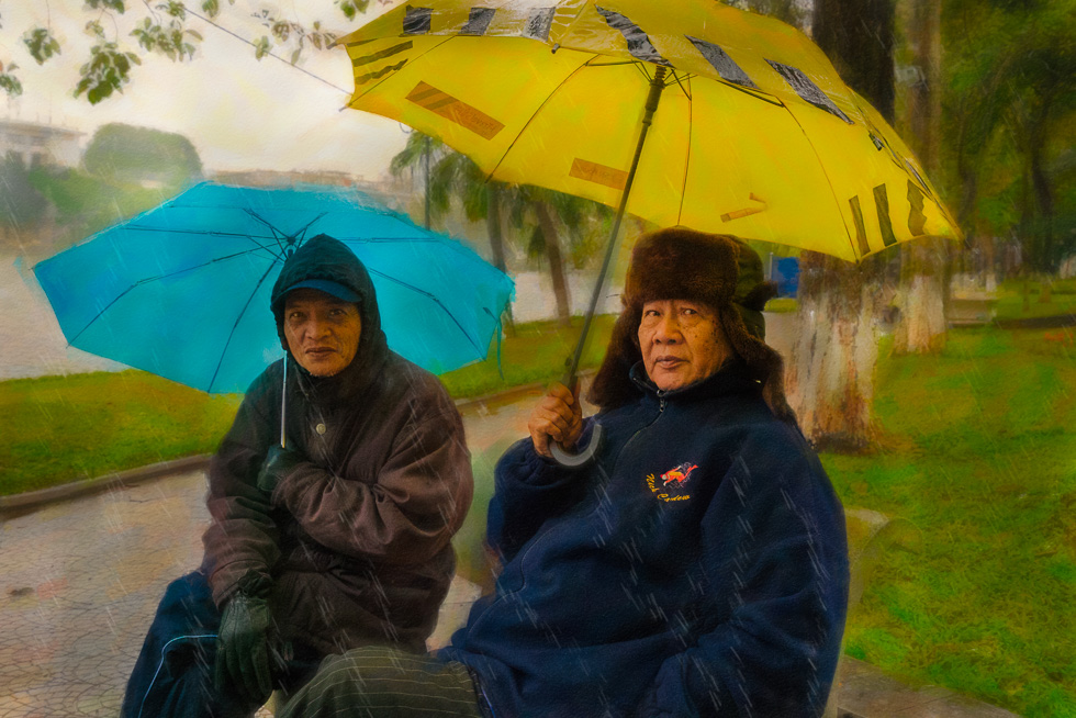 Two Vietnamese elders grinning at the dumb foreigner walking unprotected through the rain