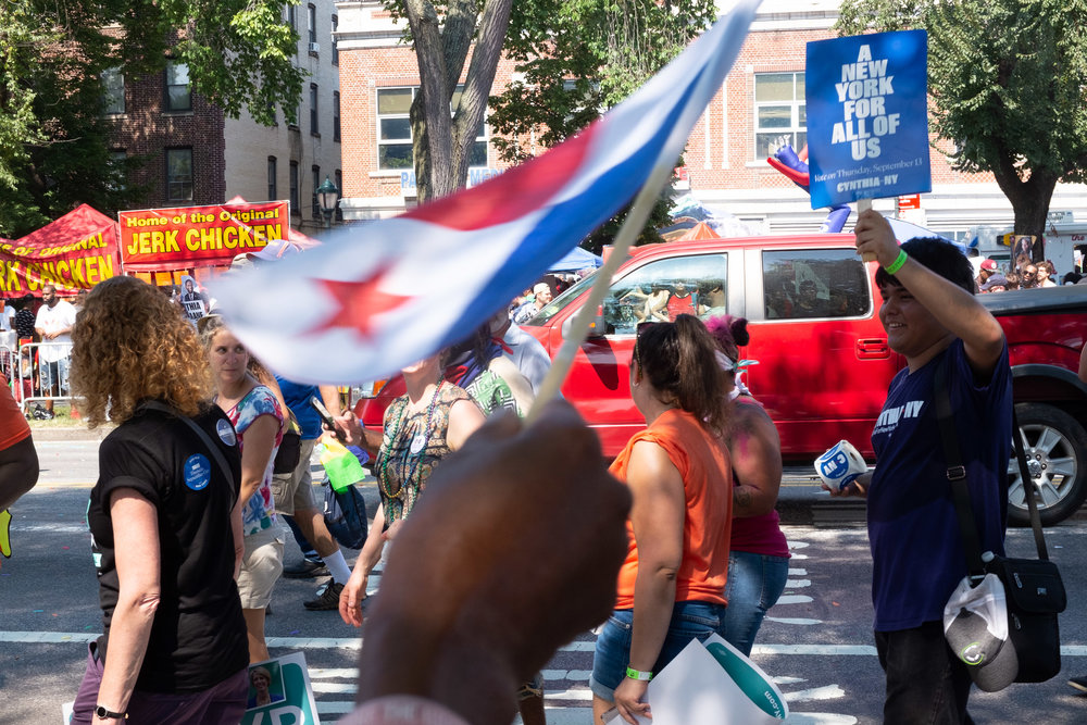 Perfectly obscured by this flag, is candidate for governor of New York, Cynthia Nixon