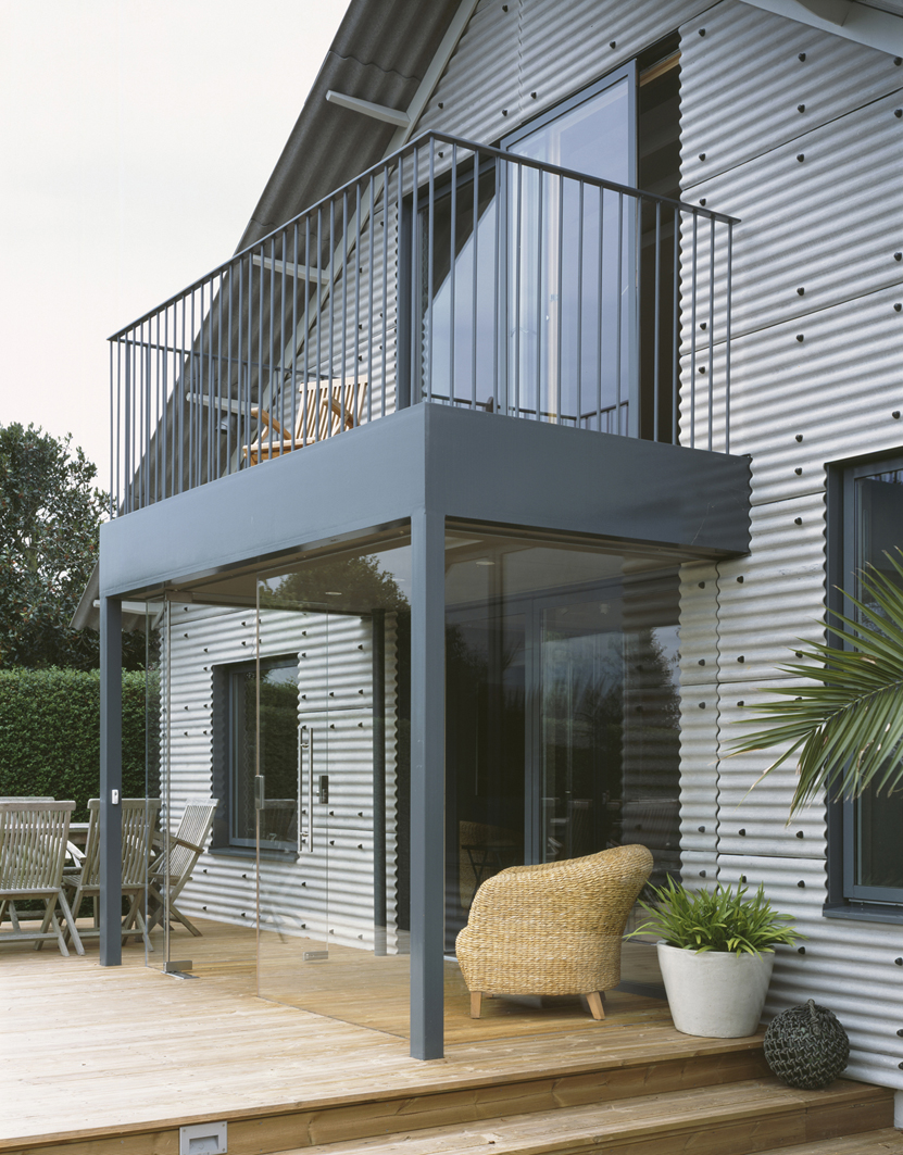 The utilitarian aspect of the material is balanced with a sense of luxury given by the generosity of a modern interpretation of a Victorian porch as well as carefully framing the views over Chichester Harbour and precise detailing.  We swiftly achieved planning for this challenging design by cleverly using the permitted development rights. (the site is part of the Chichester Harbour Conveyancy). Since seeing the completed scheme they have been convinced and are going to use this project as a good practice example of a sensitive development in this landscape.